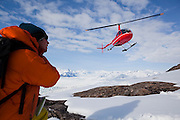 Ian Howat, glaciologist with Ohio State University, watches as a helicopter comes in for landing at the Columbia Glacier, near Valdez, Alaska.