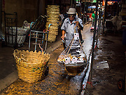 01 APRIL 2014 - BANGKOK, THAILAND: A snack vendor carries his traditional yoke and baskets through the flower market in Bangkok. The Yodpiman Flower Market (also called Pak Khlong Talat) is being renovated and gentrified. The market opened in 1961 and has been a Bangkok landmark for more than 50 years, is being turned into a high end mall. Many of the flower and vegetable vendors in the market may be forced out.    PHOTO BY JACK KURTZ