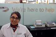 A smiling female member of staff at the British Airways information desk in Departures at Heathrow Airport's Terminal 5.