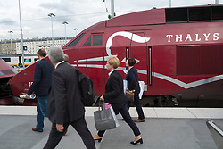 Passengers on platform next to Thalys high speed train at Gare du nord station in Paris France