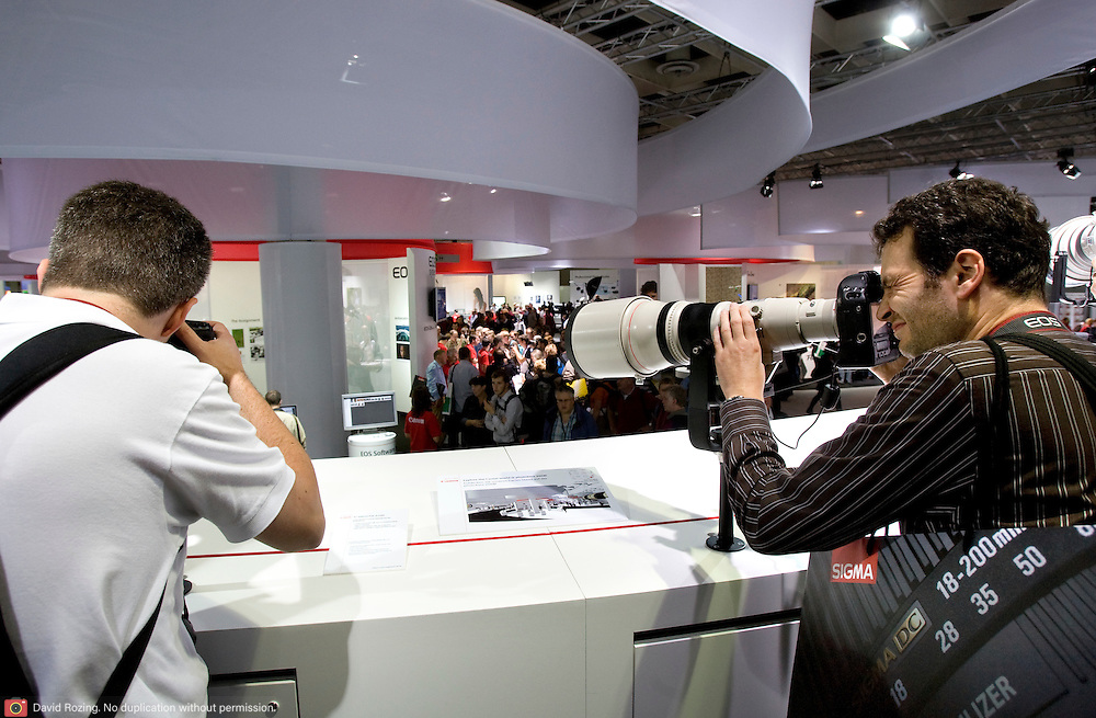 Germany, Koln 27 september 2008 20080927 Foto: David Rozing ..Photokina 2008, grootste vakbeurs voor fotografie. Bezoekers proberen super telelenzen uit. Canon stand, canon introduceerde de 5d Mark II op deze beurs ..Photokina 2008 Koln, largest traide fair in imaging sector.Canon stand, canon introduced the 5d mark II on this fair..photokina 2008 presents the future of worldwide image communication..1,523 suppliers from 49 countries at the World of Imaging.66 percent from abroad.Companies exhibiting at larger stands in Cologne.More than 200 new exhibitors.photokina strengthens its position as the leading international trade fair for the entire imaging sector.Fair to feature outstanding supporting program..Foto David Rozing