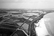 Nederland, Noord-Brabant, Werkendam, 01-04-2016; <br /> Ruimte voor de Rivier project Ontpoldering Noordwaard. <br /> Foto richting Biesbosch, rivier de Nieuwe Merwede rechtsonder. De bandijk (winterdijk) is  voorzien van doorlaten annex brug, boerderijen zijn op terpen gebouwd. De dijken aan de rivierzijde zijn gedeeltelijk afgegraven waardoor rivier de Nieuwe Merwede bij hoogwater via de Noordwaard sneller naar zee stromen. Gevolg van de ingrepen is dat de waterstand verder stroomopwaarts zal dalen. Ook de getijden keren terug in het gebied.<br /> National Project Ruimte voor de Rivier (Room for the River) By lowering and moving the dike of the Noordwaard polder the area will become subject to controlled inundation and function as a dedicated water detention district. Houses and farmhouses will be constructed on new dwelling mounds.<br /> <br /> luchtfoto (toeslag op standard tarieven);<br /> aerial photo (additional fee required);<br /> copyright foto/photo Siebe Swart