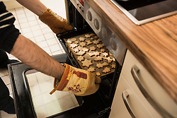 Close-up of a man taking out baked cookies from the oven, Munich, Bavaria, Germany