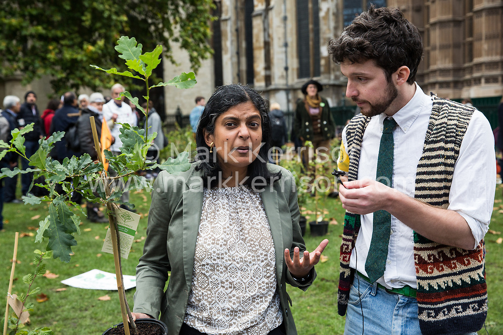 London, UK. 8 October, 2019. Rupa Huq, Labour MP for Ealing Central and Acton, receives a tree from Extinction Rebellion climate activists in Old Palace Yard on the second day of International Rebellion protests. Activists created a fledgling forest of potted native trees outside Parliament as part of an initiative named Reforest Earth and they were then presented to MPs to call on the government to plant billions of trees across the UK and support the planting of trillions more around the world.