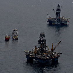 Oil is seen on the surface of the water around the Transocean Development Driller II (top) and Transocean Development Driller III (bottom), which are both drilling a relief wells, at the site of the Deepwater Horizon oil spill in the Gulf of Mexico near the coast of Louisiana, U.S., on Wednesday, June 2, 2010. BP Plc has given up trying to plug its leaking well in the Gulf of Mexico any sooner than August, laying out a series of steps to pipe the oil to the surface and ship it ashore for refining, said Thad Allen, the U.S. government's national commander for the incident. Photographer: Derick E. Hingle