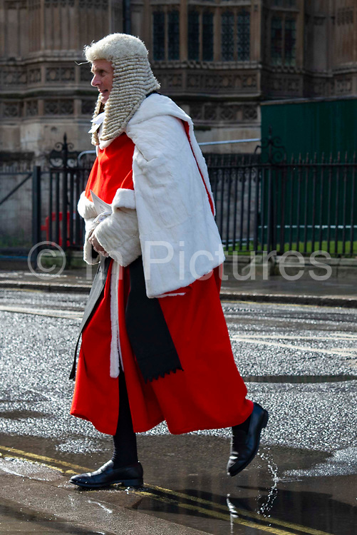 A judge walks through a puddle towards the  Palace of Westminster following the annual Judges Service which marks the start of the new legal year at Westminster Abbey in London, United Kingdom on 1st October 2019.