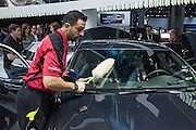 New York, NY - 1 April 2015. A man from a detailing company dusts a new Cadillac at the New York International Auto Show. Crews of cleaners were busy throughout the opening day.