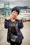 Woman at Yeosu harbour in South Korea is posing for a photograph.