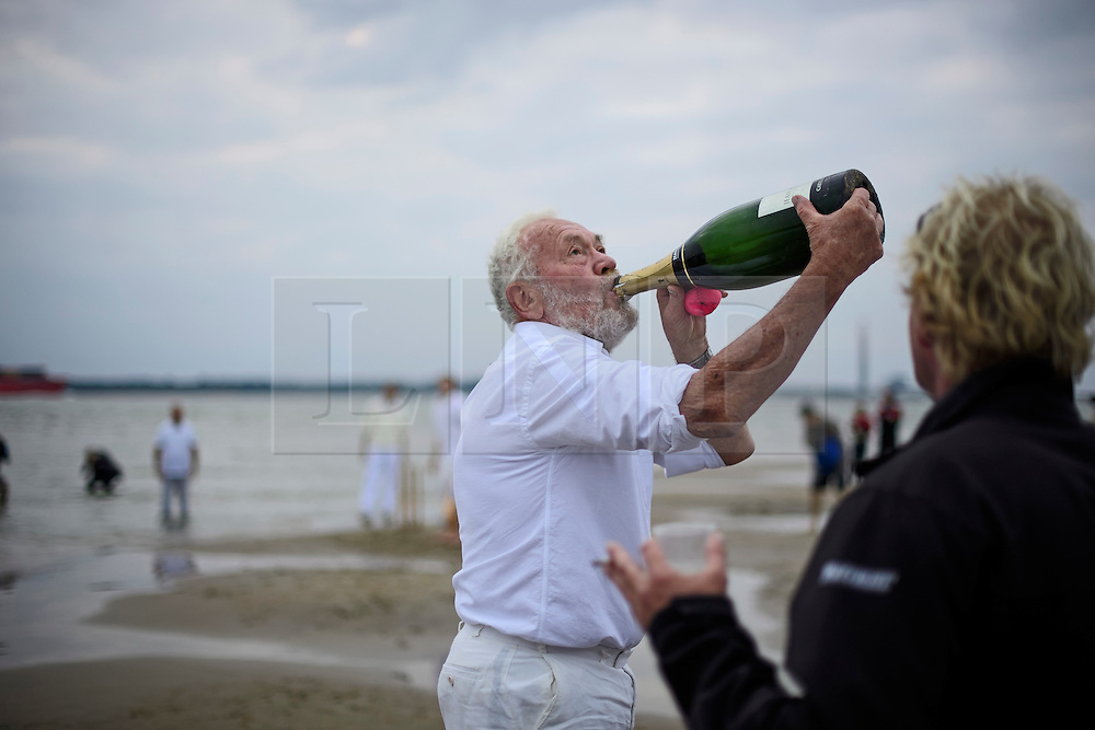 © Licensed to London News Pictures. 18/09/2016. Portsmouth, UK. A bowler takes a quick swig of champagne before bowling. Teams take part in the  Bramble Bank Cricket Match in the middle of The Solent strait on September 18, 2016. The annual cricket match between the Royal Southern Yacht Club and The Island Sailing Club, takes place on a sandbank which appears for 30 minutes at lowest tide. The game lasts until the tide returns. Photo credit: Ben Cawthra/LNP