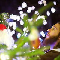 """Michael Grant, 28, """"Philly Jesus,"""" adjusts Christmas ornaments with his walking staff at Rittenhouse Park in Philadelphia, PA on December 14, 2014.  Nearly everyday for the last 8 months, Grant has dressed as Jesus Christ, and walked the streets of Philadelphia to share the Christian gospel by example.  He quickly acquired the nickname of """"Philly Jesus,"""" which he has gone by ever since."""