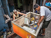 05 OCTOBER 2015 - BANGKOK, THAILAND: BOONAK TANGAON, 77, (left) and her husband, SAWAT TANGAON, 70, pack up their belongings in their home in the Wat Kalayanamit neighborhood. They've raised two children and hour grandchildren in their home. They are being evicted. Fifty-four homes around Wat Kalayanamit, a historic Buddhist temple on the Chao Phraya River in the Thonburi section of Bangkok, are being razed and the residents evicted to make way for new development at the temple. The abbot of the temple said he was evicting the residents, who have lived on the temple grounds for generations, because their homes are unsafe and because he wants to improve the temple grounds. The evictions are a part of a Bangkok trend, especially along the Chao Phraya River and BTS light rail lines. Low income people are being evicted from their long time homes to make way for urban renewal.        PHOTO BY JACK KURTZ
