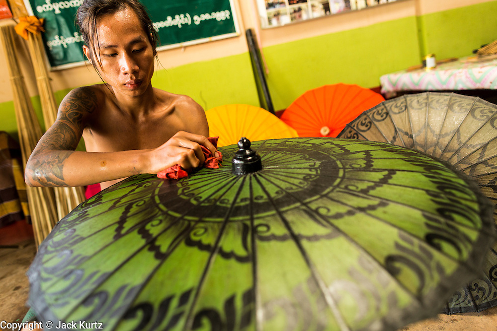 14 JUNE 2013 -  PATHEIN, AYEYARWADY, MYANMAR: A worker varnishes waterproof umbrellas at the Shwe Sar umbrella factory in Pathein. Pathein is a center of the Burmese umbrella and parasol industry. Most are actually parasols made in the traditional Burmese way using treated paper which is not water proof. Shwe Sar's umbrella's are made with treated cloth and are waterproof. Since US and European sanctions have been lifted businesses in Myanmar have seen an explosion in exports. Shwe Sar exports most of their umbrellas to Europe. Pathein, sometimes also called Bassein, is a port city and the capital of the Ayeyarwady Region, Burma. It lies on the Pathein River (Bassein), which is a western branch of the Irrawaddy River. It's the fourth largest city in Myanmar (Burma) about 190 km west of Yangon.    PHOTO BY JACK KURTZ