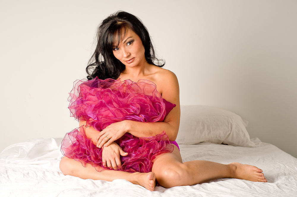 Sexy boudoir portrait of woman holding a pink pillow sitting on bed