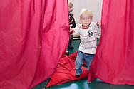 Nederland, Helmond, 20091111...Kinderdagverblijf de Bereboot is een nieuw kdv dat is gestart op een landgoed in een mooie ruime en groene omgeving.  ..Spelen in de gymzaal. Jongentje houdt de gordijnen van het theatertje vast.....Netherlands, Helmond, 20091111. ..Childcare, The nursery the Bear boot is on an estate in a beautiful and spacious green surroundings.