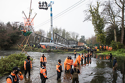 HS2 security guards form a line across the river Colne in front of Dan Hooper, widely known as Swampy during the 1990s, and a large cherry picker containing enforcement agents on 8th December 2020 in Denham, United Kingdom. The climate and roads activist had occupied a bamboo tripod positioned in the river the previous day in order to delay the building of a bridge as part of works for the controversial HS2 high-speed rail link and a large security operation involving officers from at least three police forces, the National Eviction Team and HS2 security guards was put in place to facilitate his removal.