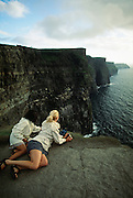 Girls looking over the edge of Cliffs of Moher, Ireland