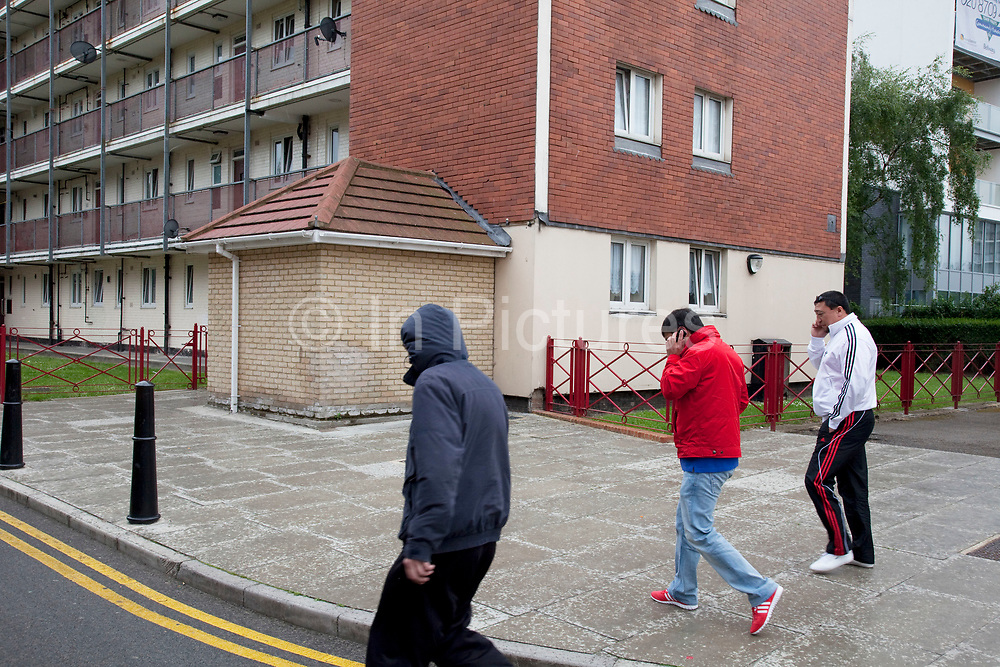 Eastern European men walk near to council flats in Tower Hamlets, East London. Many people are at risk of losing their homes in London with the introduction of new benefit rules, which may push many people renting or who own council apartments out of the city. Tower Hamlets is a poor and over populated borough with many people living in small homes in high rise apartment blocks.