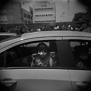 A kid looks out of the window of a car after her family queued for five hours to receive a box of food from the local authorities in the Iztapalapa municipality, in Mexico City on May 13, 2020. The working-class district has been one of the most affected in the country.
