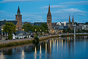 "Lights of Inverness reflect in River Ness at twilight, seen from Friars' Bridge, in Scotland, United Kingdom, Europe. Inverness is the administrative capital of the Highlands. A settlement was established here by the 500s AD with the first royal charter being granted by King David I in the 1100s. The Gaelic king Mac Bethad Mac Findláich (MacBeth) whose 11th-century killing of King Duncan was immortalised in Shakespeare's largely fictionalized play Macbeth, held a castle within the city where he ruled as Mormaer of Moray and Ross. Inverness lies near two important battle sites: the 11th-century battle of Blàr nam Fèinne against Norway which took place on The Aird and the 18th-century Battle of Culloden which took place on Culloden Moor. Inverness means ""Mouth of the River Ness"" in Scottish Gaelic. Surveys place it as one of the happiest places in the UK."