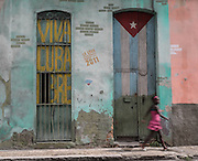 A young woman walks past a  colorful wall in Centro Habana, Cuba.