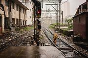 A woman covers her head as she crosses the railway tracks during a monsoon rain storm, Chhatrapati Shivaji Terminus (CST), Mumbai, India