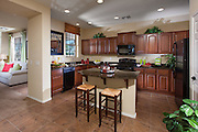 Model Home Kitchen with Tile Flooring and Cherry Wood Cabinets