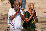 Indian Hindu couple bathing and praying in the River Ganges by Kshameshwar Ghat in holy city of Varanasi, India