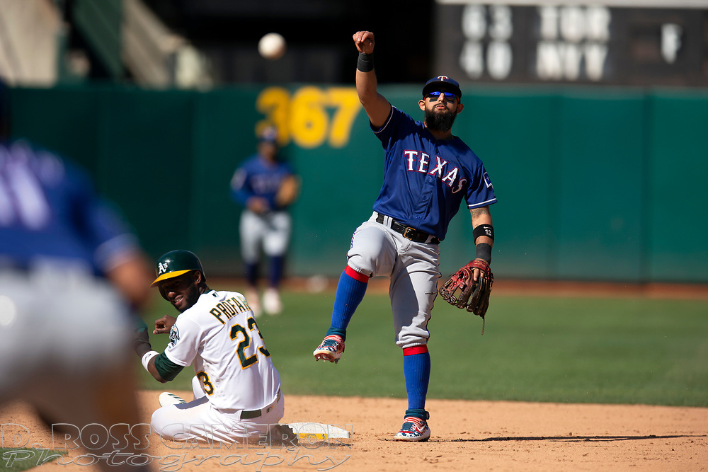 Texas Rangers second baseman Rougned Odor, right, throws over Oakland Athletics' Jurickson Profar (23) to complete a double play during the sixth inning of a baseball game, Sunday, Sept. 22, 2019, in Oakland, Calif. Sean Murphy was out at first. (AP Photo/D. Ross Cameron)
