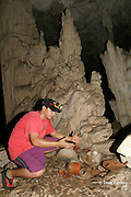 guide exhibits shards of ancient Mayan pottery at Crystal Cave, on the grounds of Jaguar Paw Jungle Resort, Cayo District, Belize, Central America MR 335