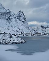 Mountians rise above frozen bay in Reine harbor, Reine, Moskenesøy, Lofoten Islands, Norway