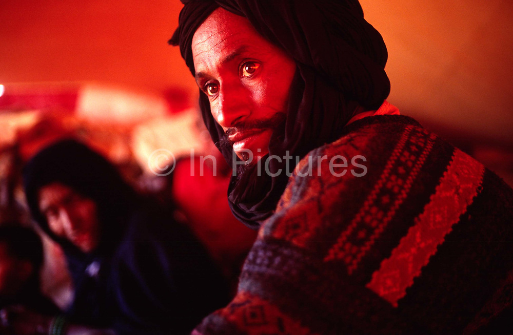 A nomad man entertains guests from the desert in his tent in the Sahara Desert, Mauritania.