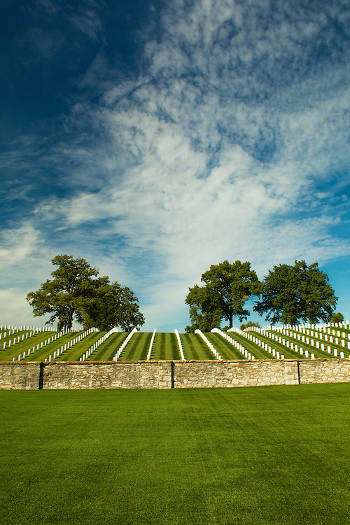 An uphill view at Jefferson Barracks as blue skies and wispy clouds cover the velvet green grass and headstones