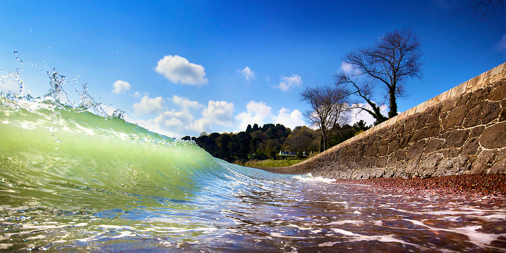Green wave rising up over red pebbles on a sunny day at St Catherine's Bay on the east coast of Jersey Channel Islands