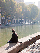 Man sitting by the Canal Saint Martin, Paris, France