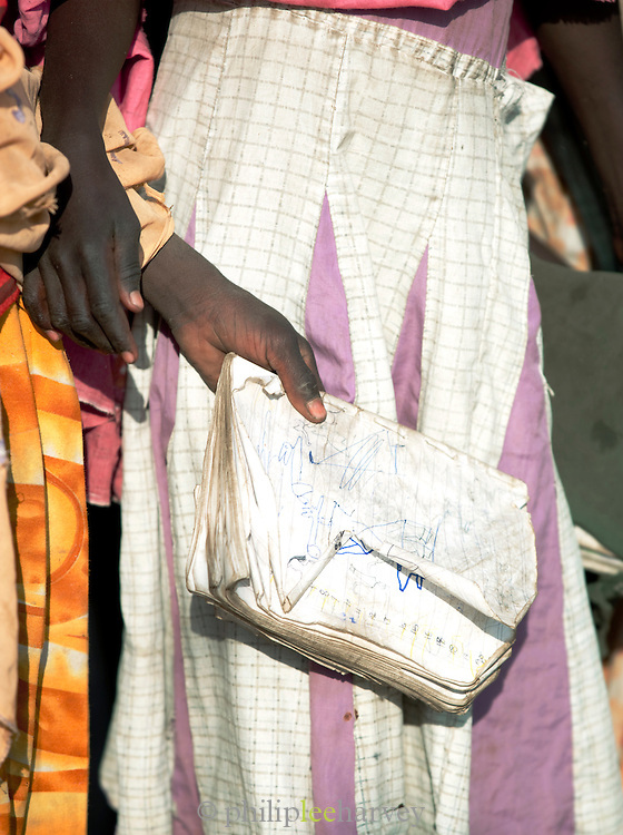 A child of the Nuba tribe holds a notebook with drawings, village of Nyaro, Kordofan region, Sudan