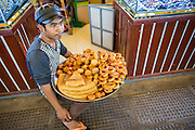 """30 JANUARY 2013 - PHNOM PENH, CAMBODIA:  A bakery vendor in the Central Market in Phnom Penh. The Central Market (""""Psah Thom Thmey"""", """"New Grand Market""""), is a large market constructed in 1937 in the shape of a dome with four arms branching out into vast hallways with stalls of goods. It opened in 1937, and was the biggest market in Asia at the time; today it still operates as a market. It was renovated from 2009 to 2011.     PHOTO BY JACK KURTZ"""