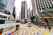 Historic double decker trams travel past the Landmark Building in the central district of Hong Kong.