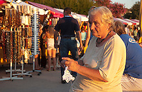 Eine alte Frau wartet im Licht der untergehenden Sonne häkelnd auf Kundschaft an der Promenade von Porec, Istrien, wo ein Souvenirstand neben dem anderen steht. | On the beach promenade of Porec in the croatian peninsula of Istria. An old woman sits in the light of the setting sun, knitting and waiting for costumers buying her wares. Souvenir and gift stands in the back.