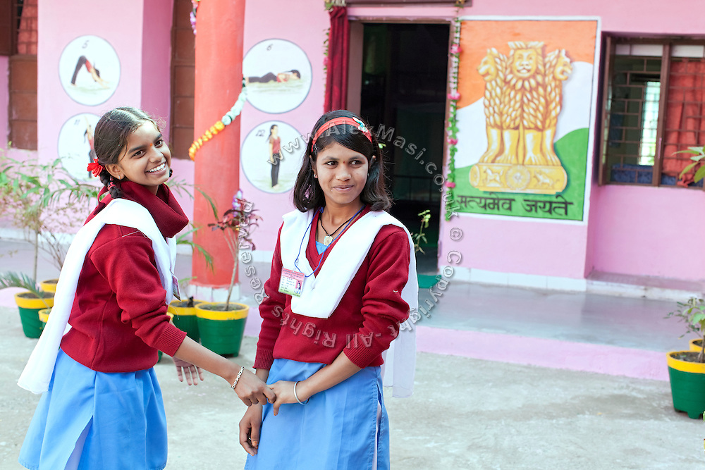 Ritu Gaur, 13, (right) is holding the hand of her best friend, Aruna, 13, while standing inside the Jamoniya Tank Girls Hostel, near Sehore, Madhya Pradesh, India, where the Unicef India Sport For Development Project has started in 2012. Covering 313 state-run girls' hostels and 207 mixed hostels in Madhya Pradesh, the project ensures that children from Scheduled Tribes (ST) and others amongst the poorest people in India, can easily access education and be introduced to sports. Field workers from Unicef also oversee their nutrition and monitor the overall conditions of each pupil.