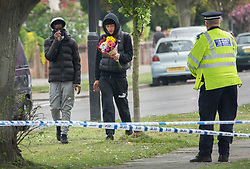 © Licensed to London News Pictures. 12/04/2017. London, UK. A youth carries flowers near where a 19 year old man, named locally as Abdullahi Tarabai,  was murdered yesterday after reportedly being chased though a housing estate in Northolt. This is the second fatal stabbing in the capital in 24 hours. The location is adjacent to a gun siege from October 2016. Four men have been arrested Photo credit: Peter Macdiarmid/LNP
