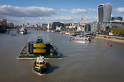 A tug tows a heavy crane downstream on the Thames, passing on the right, the Walkie-Talkie building in the City of London, on 6th October 2016, in London, England.