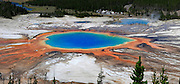 Visitors observe the colorful red bacterial mat around perimeter of Grand Prismatic Spring, Midway Geyser Basin, Yellowstone National Park, Wyoming. Noted as the largest hot spring in the U.S. and third largest in the world.