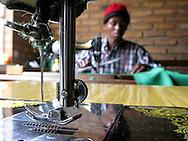 Kigali, Rwanda -A Rwandan man sews trousers using a treadle sewing machine at a business run by local church women in Kigali, Rwanda.