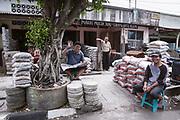 4 Friendly local men sit outside a shop.