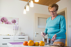 Old woman with a pot and a ladle on dining table