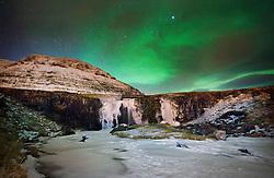 Aurora Borealis, the Northern Lights, over the Kirkjufellsfoss waterfall on the west coast of Iceland.