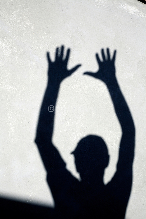 shadow of person holding up hands