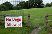 No dogs allowed sign at the local football ground on 16th August 2021 in St Dogmaels Pembrokeshire, Wales, United Kingdom. St Dogmaels is a village, parish and community in Pembrokeshire, Wales, on the estuary of the River Teifi, a mile downstream from the town of Cardigan in neighbouring Ceredigion.
