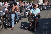 Wells Next The Sea, Norfolk, England, 08/08/2009..A pensioner on a mobility scooter passes motorcyclists at Wells summer carnival parade.