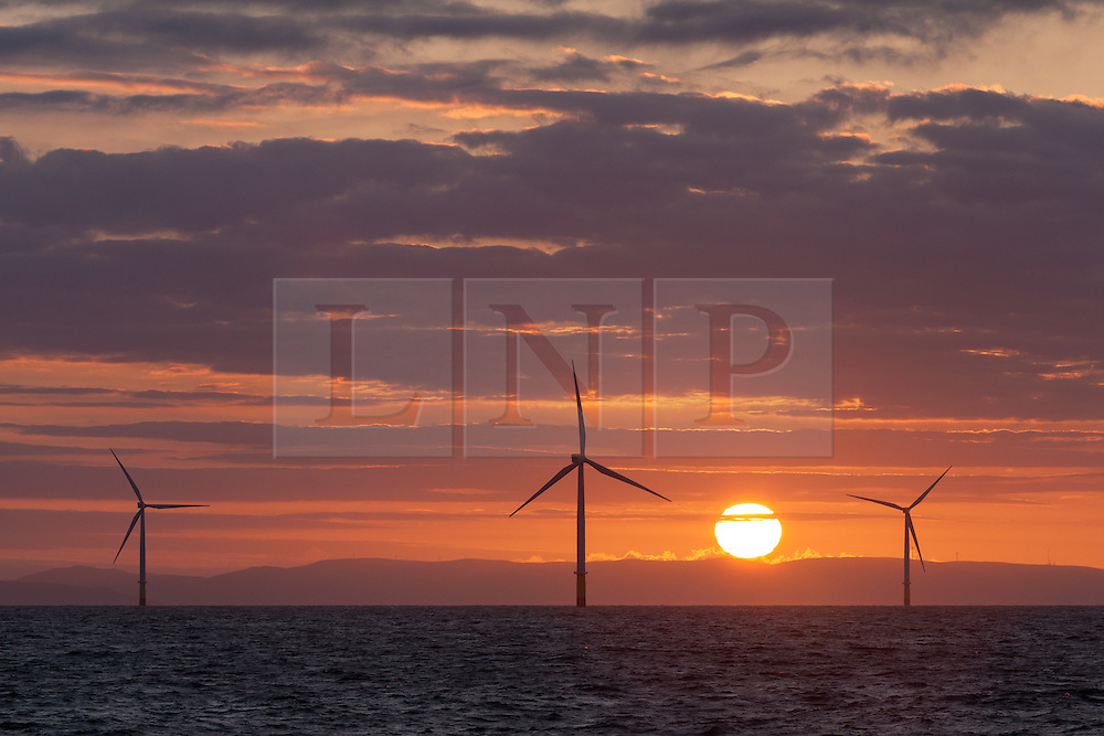 © Licensed to London News Pictures. 22/04/2016. Barrow-in-Furness, UK. Sunrise over the Walney Offshore Wind Farm, off the Cumbrian coast near Barrow-in-Furness, UK. The wind farm will soon have an extension built, which will make it the largest wind farm in the world. Photo credit : Rob Arnold/LNP